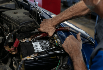 Autosmith technician servicing car battery
