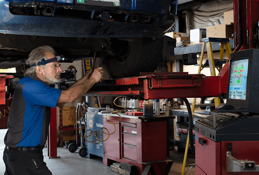Autosmith technician performing suspension and alignment maintenence