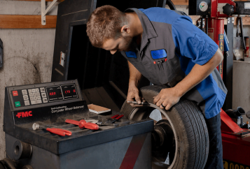 Autosmith technician examining tires for wear and tear