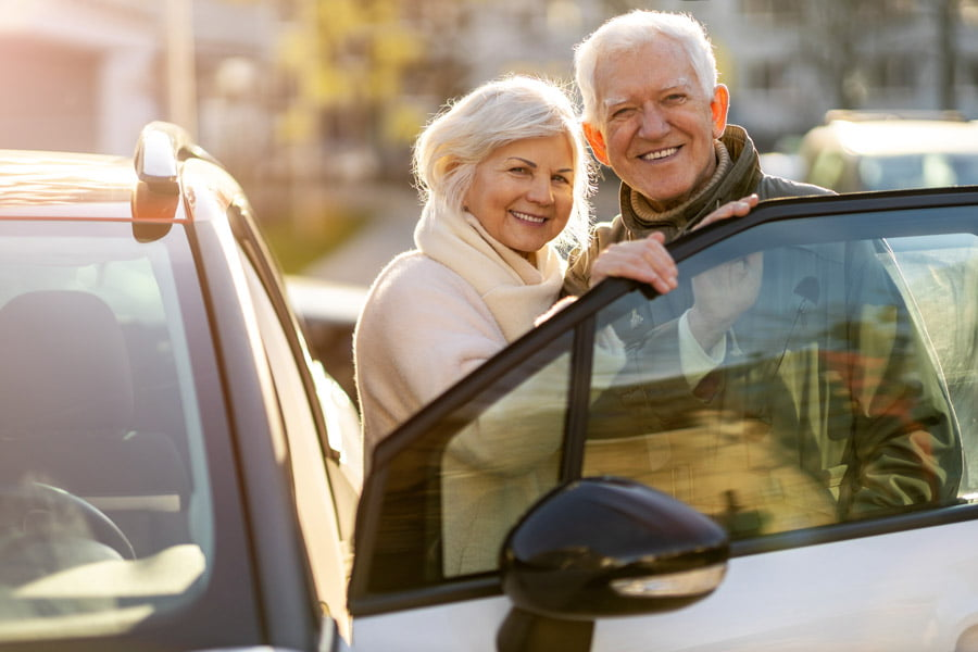 elder couple happy with their car
