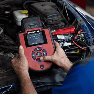 Autosmith technician testing car battery